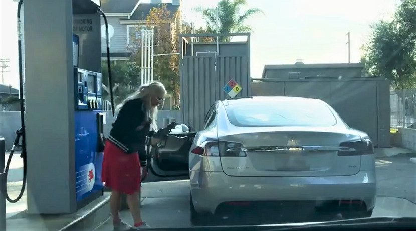 A woman tries to fill a Tesla with gasoline
